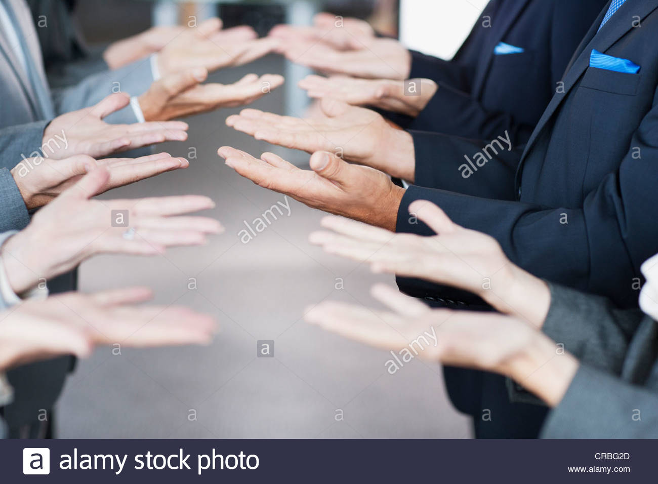 Business people standing in row with palms up - Stock Image