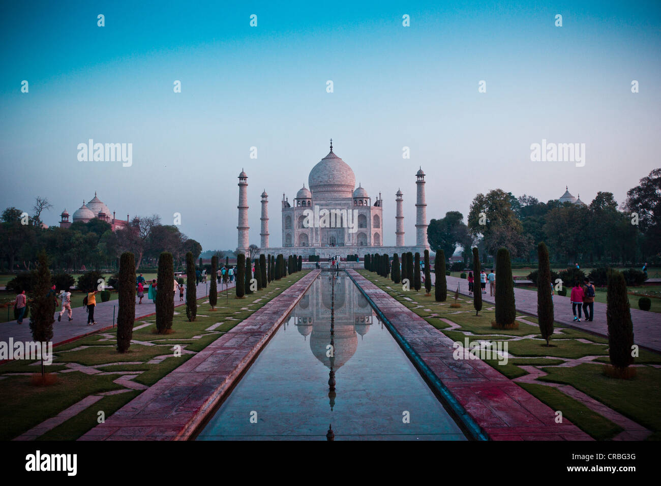 The sun rises over the Taj Mahal, taken from the end of the reflection pool. Stock Photo