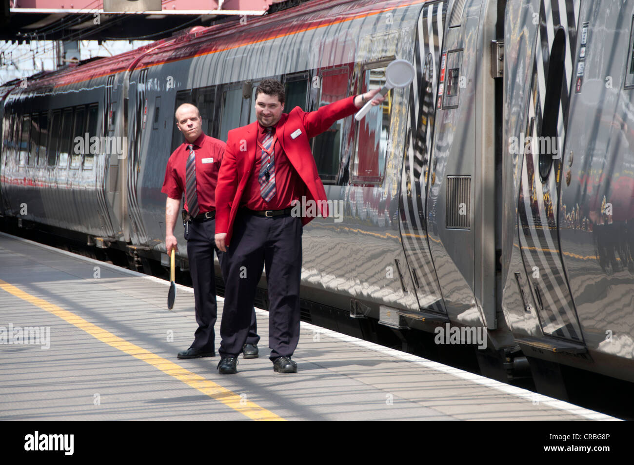 Crewe station. Virgin staff on the platform ready for the train to leave - Stock Image