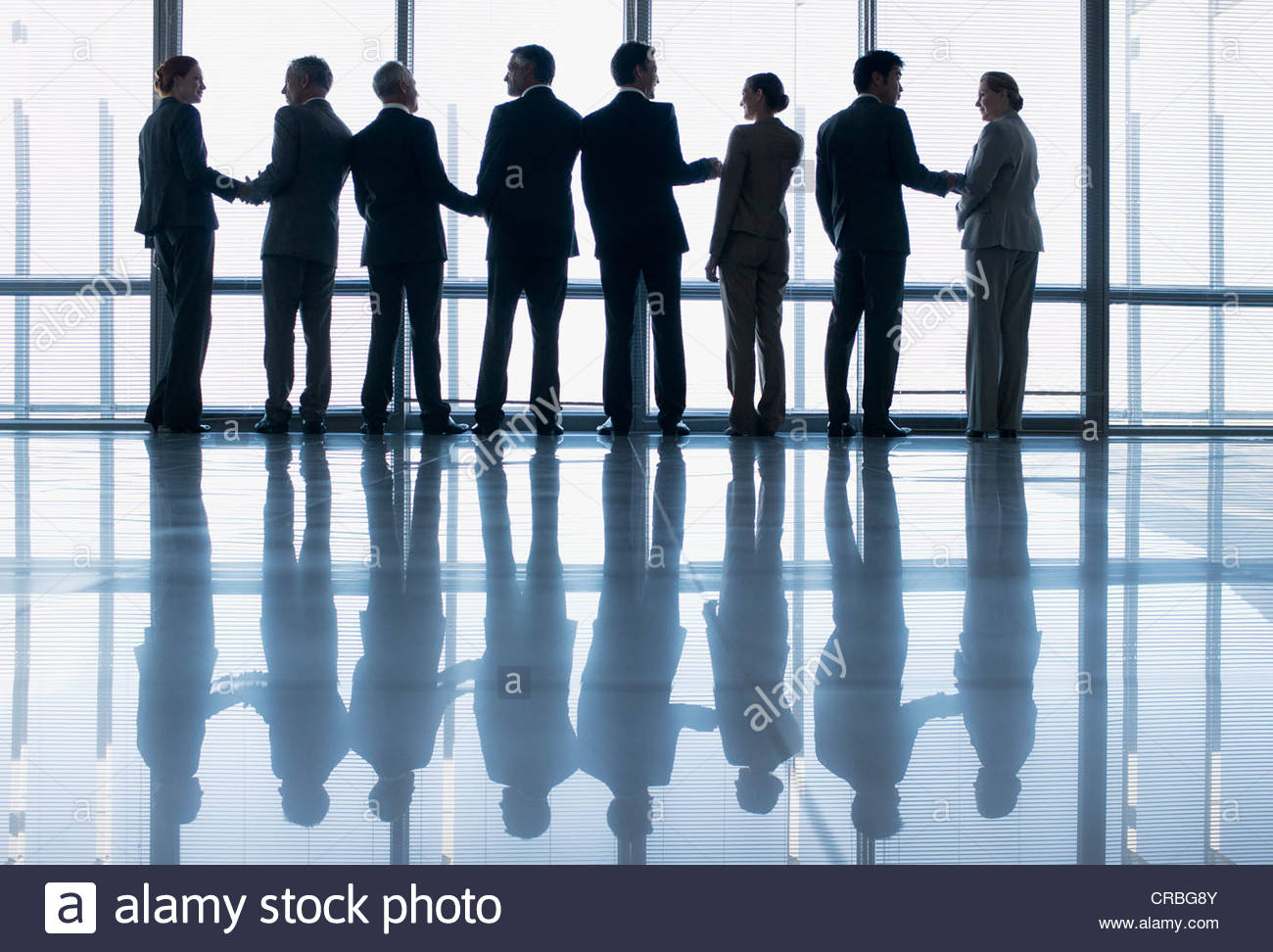 Business people shaking hands in a row at lobby window - Stock Image