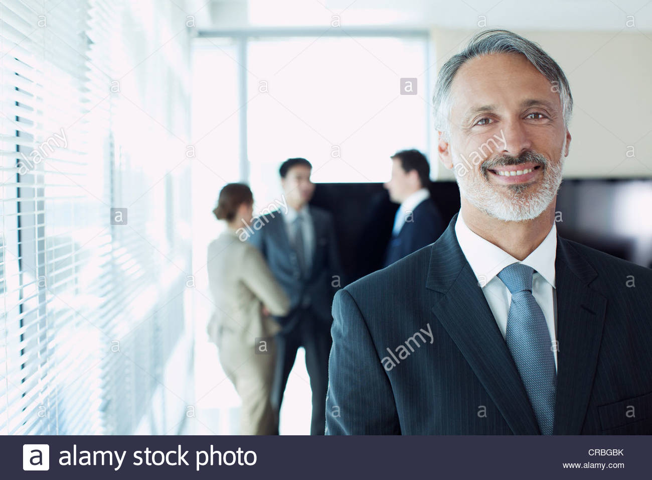 Portrait of smiling businessman with co-workers in background - Stock Image