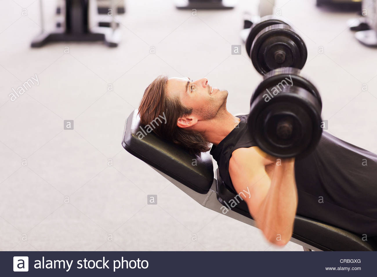 Man doing incline chest presses with dumbbells in gymnasium - Stock Image