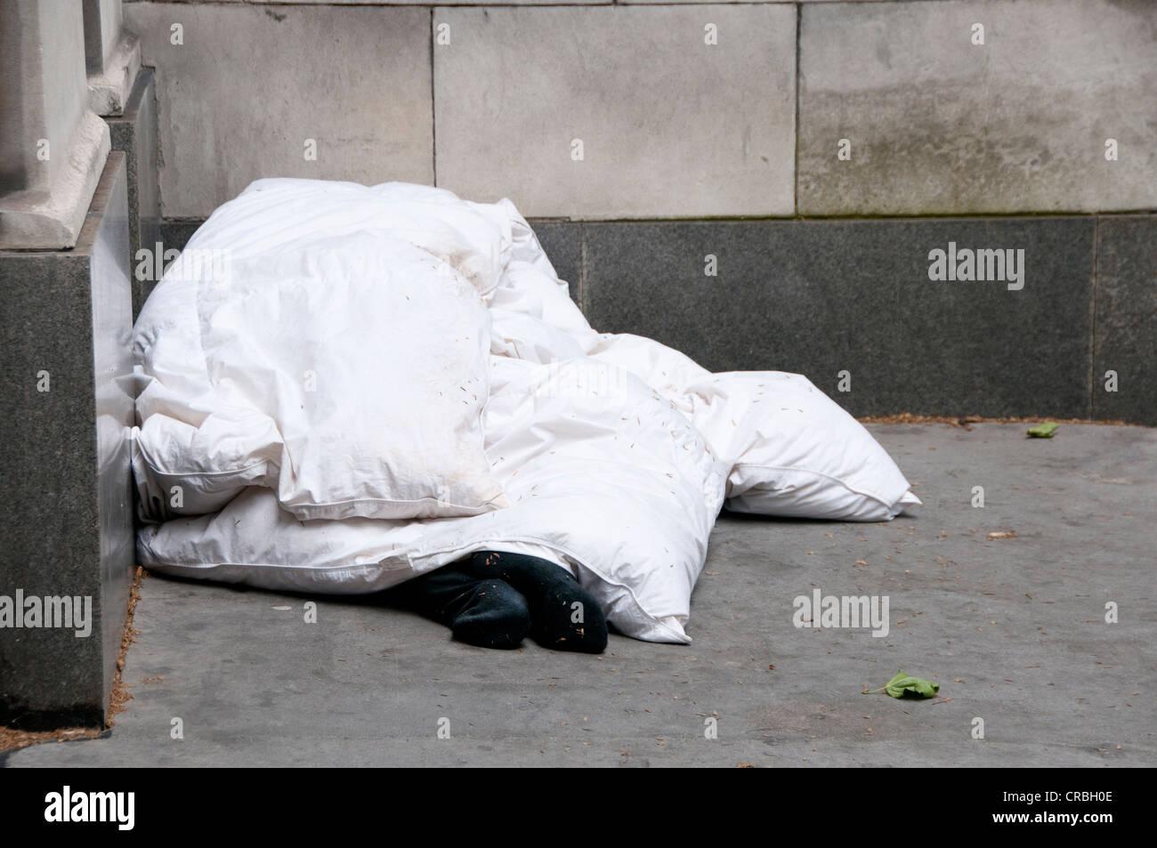 Central London. The Strand. Rough sleeper. Only socks visible under duvet - Stock Image