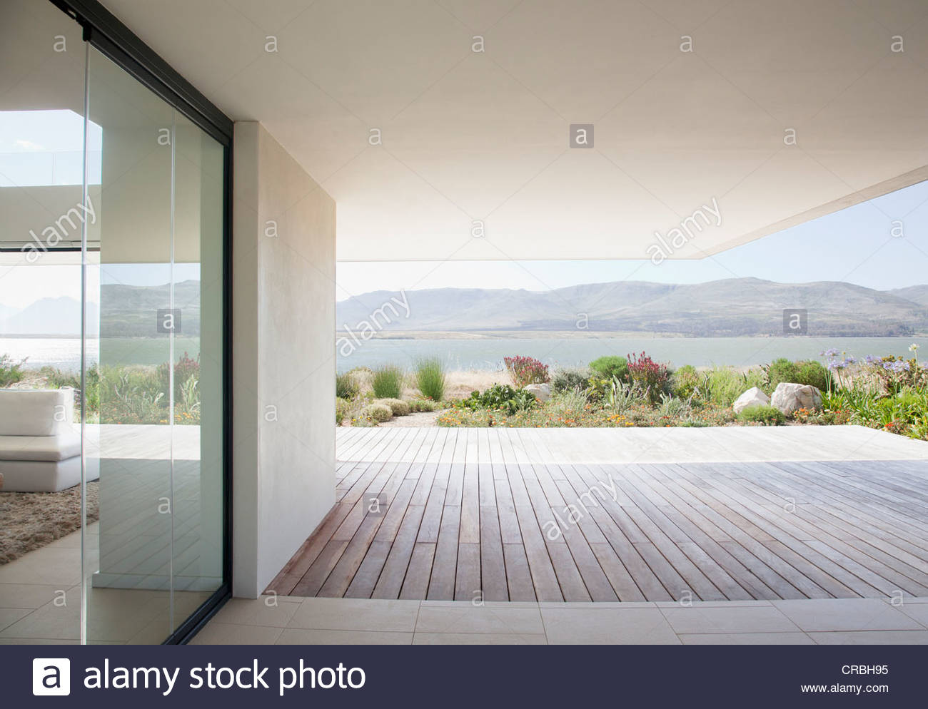 View of lake from patio of modern house - Stock Image