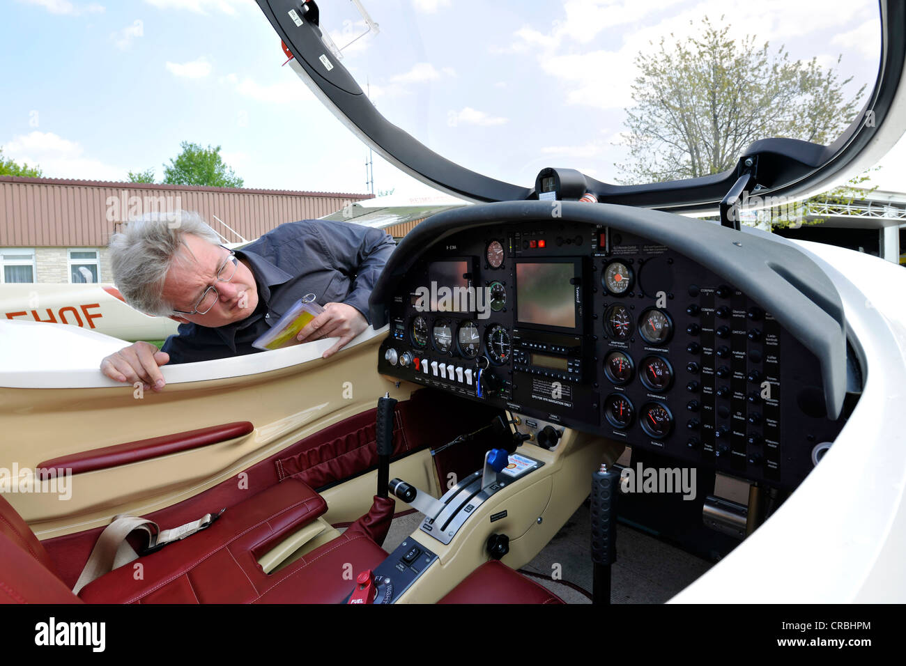 Pilot inspecting the glass cockpit of the light aircraft D-ESOA Aquila A210 AT01 with VOR Very high frequency omnidirectional - Stock Image