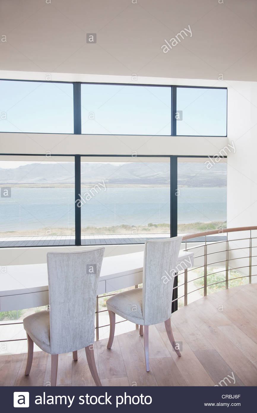 Chairs at table against railing of loft - Stock Image
