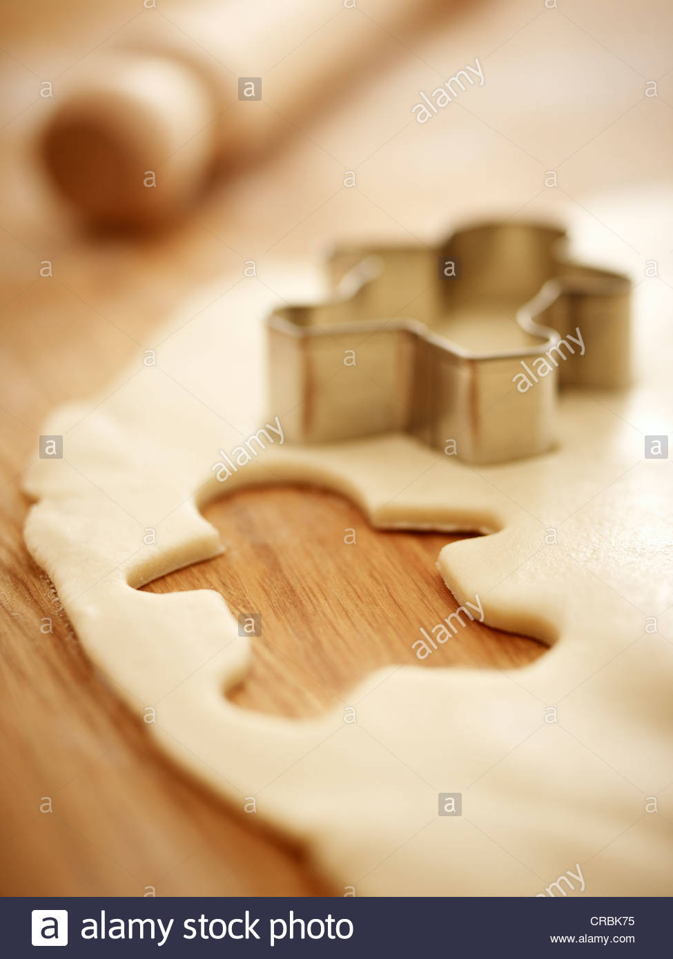 Gingerbread man cookie cutter on dough - Stock Image