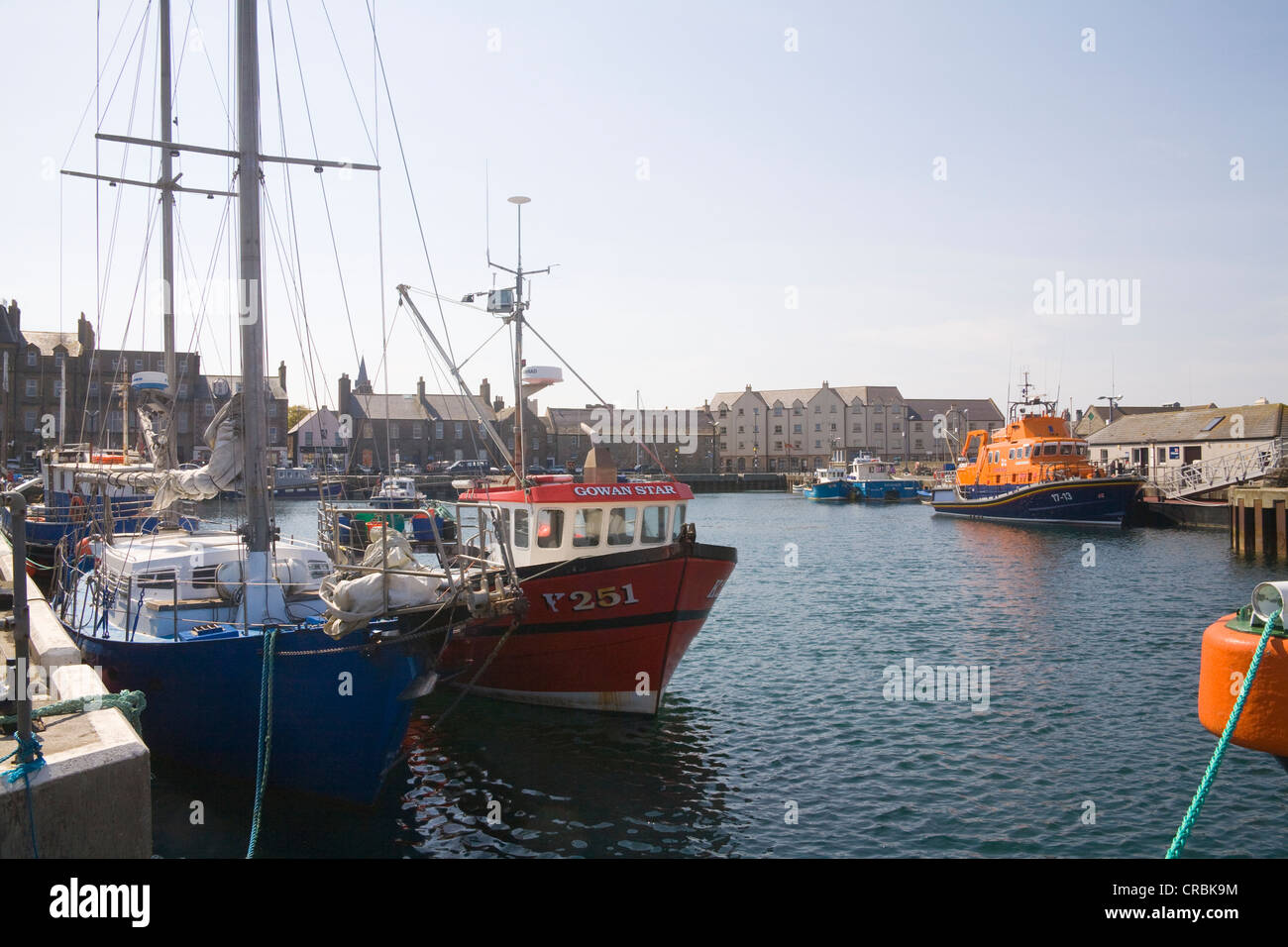 Kirkwall Orkney Mainland Scotland UK View across moored fishing boats and lifeboat to harbour side properties in - Stock Image