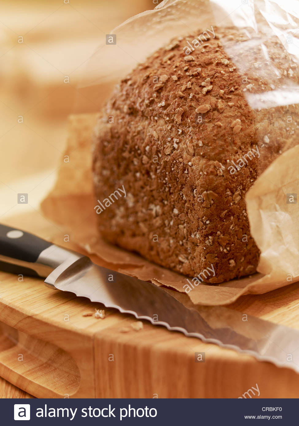 Close up of knife and loaf of bread in wrapper - Stock Image