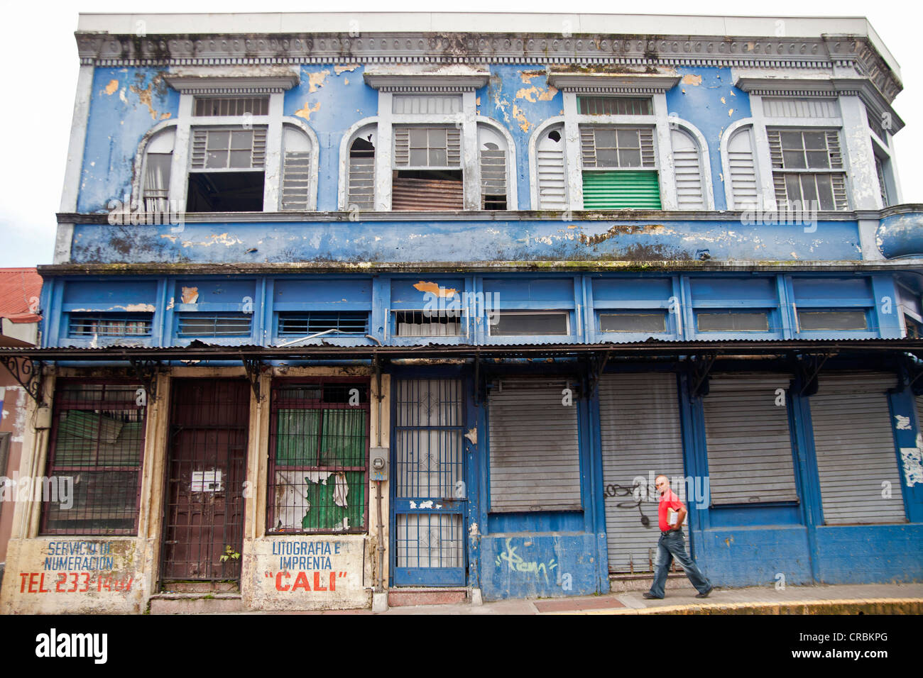 Lone passerby walking in front of a dilapidated building in the town centre of San Jose, Costa Rica, Central America - Stock Image