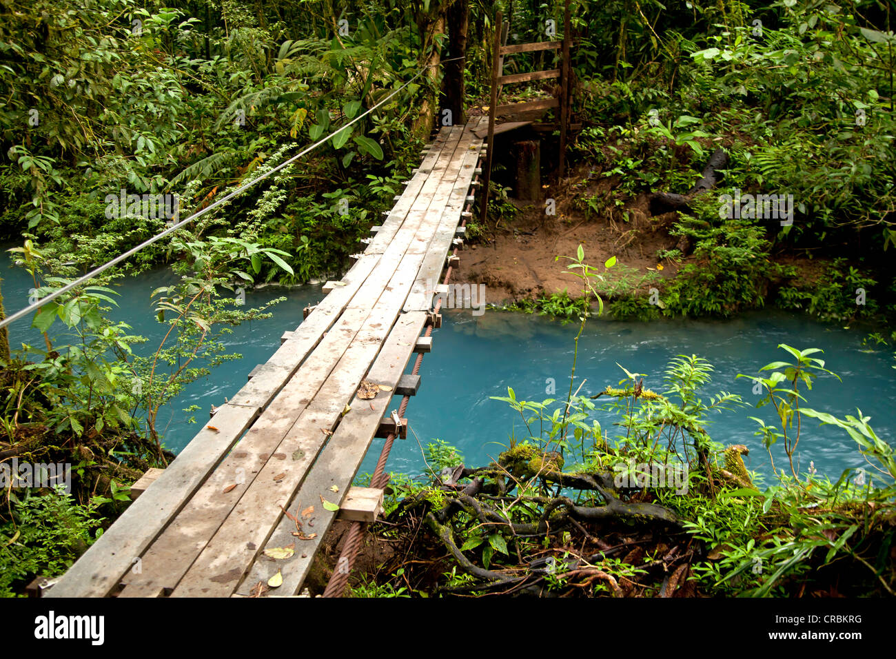 Suspension bridge over the blue waters of the Rio Celeste in Volcán Tenorio National Park, Costa Rica, Central - Stock Image