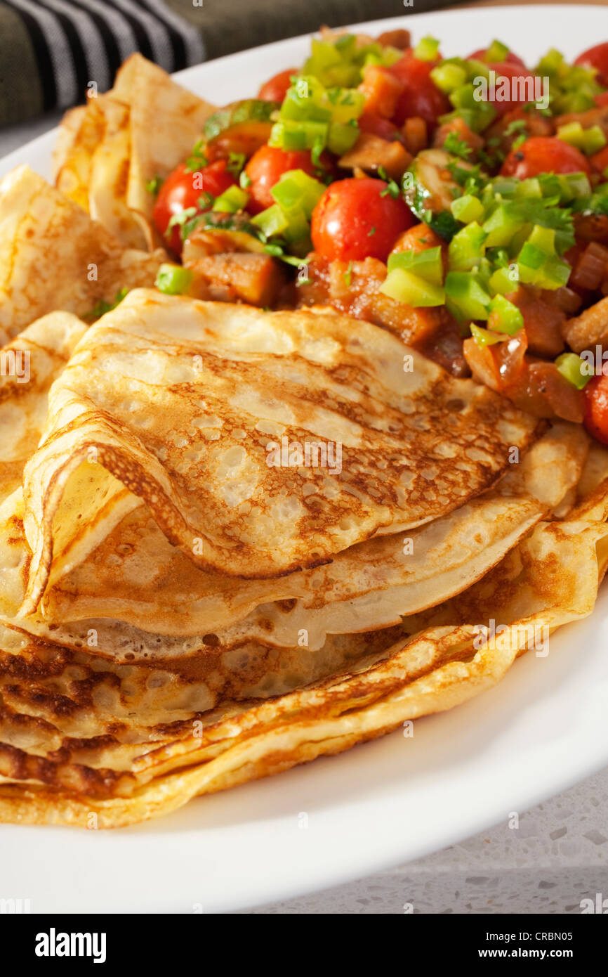 A delicious and hearty vegetarian meal of crepes or pancakes with ratatouille. - Stock Image
