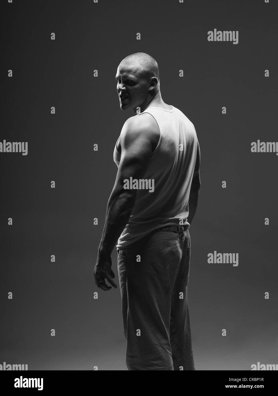 Athlete frowning over shoulder indoors - Stock Image