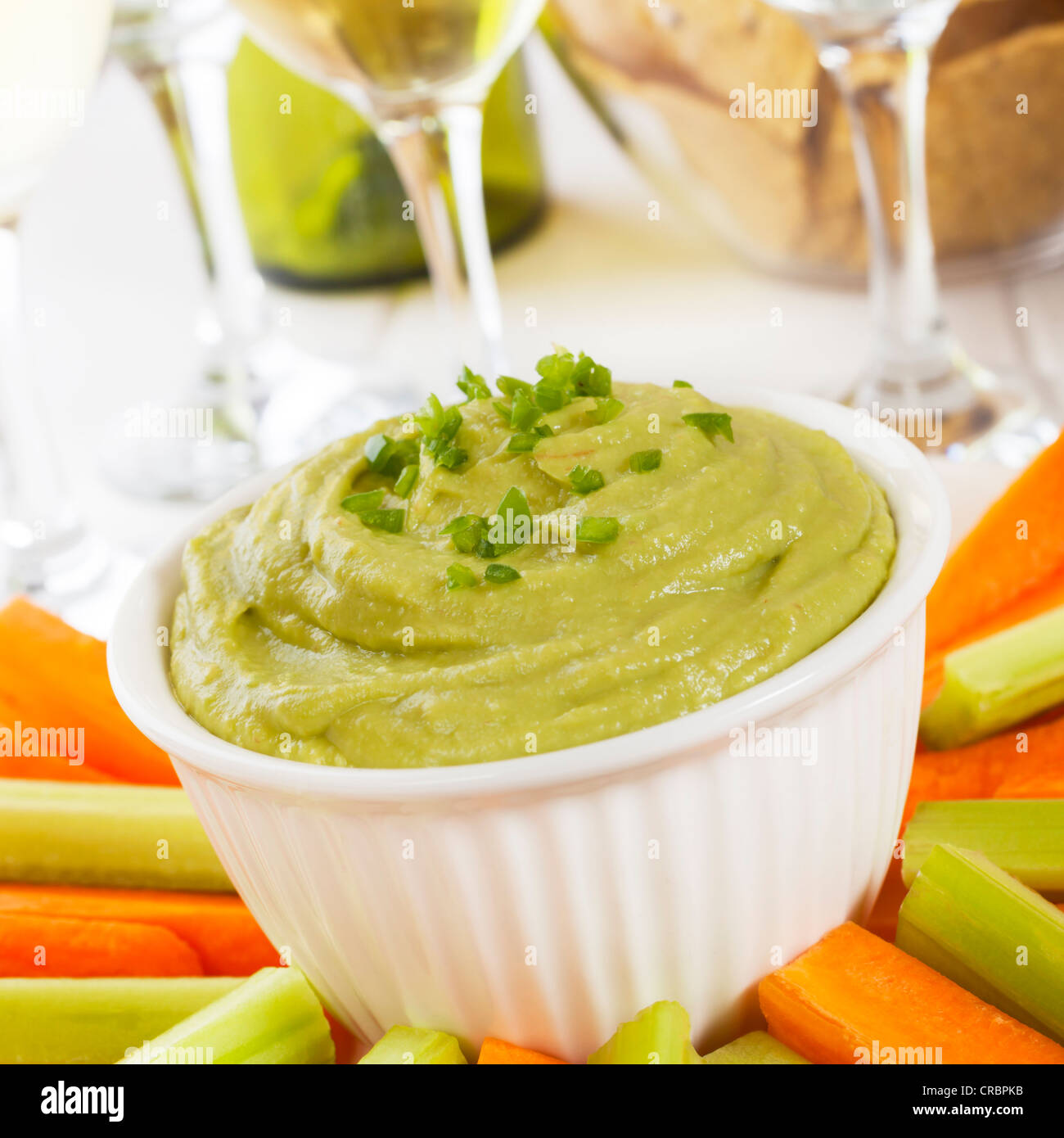 Guacamole topped with fresh green chilli, with carrot and celery sticks for dipping. - Stock Image