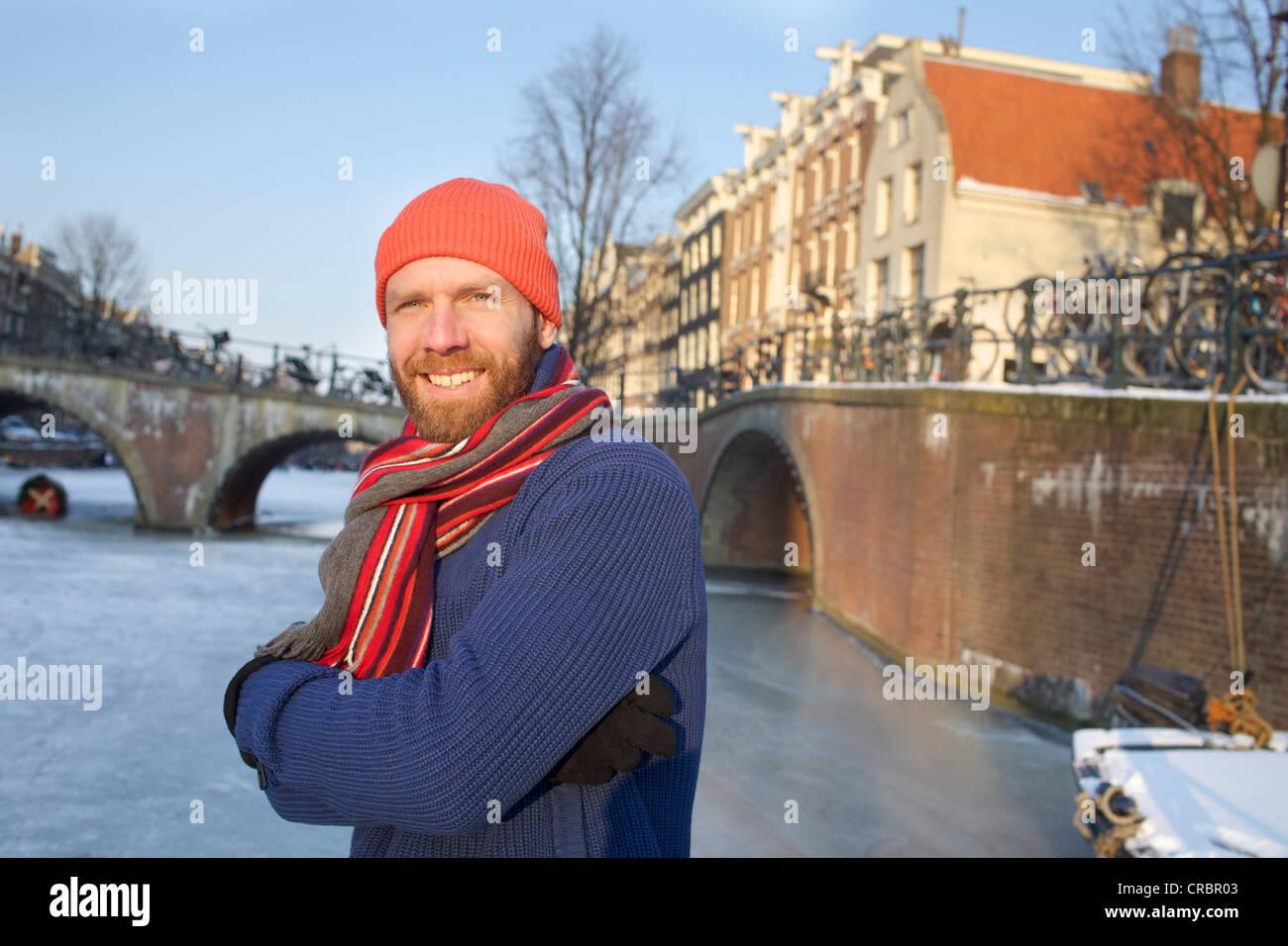 Man skating on frozen urban canal - Stock Image