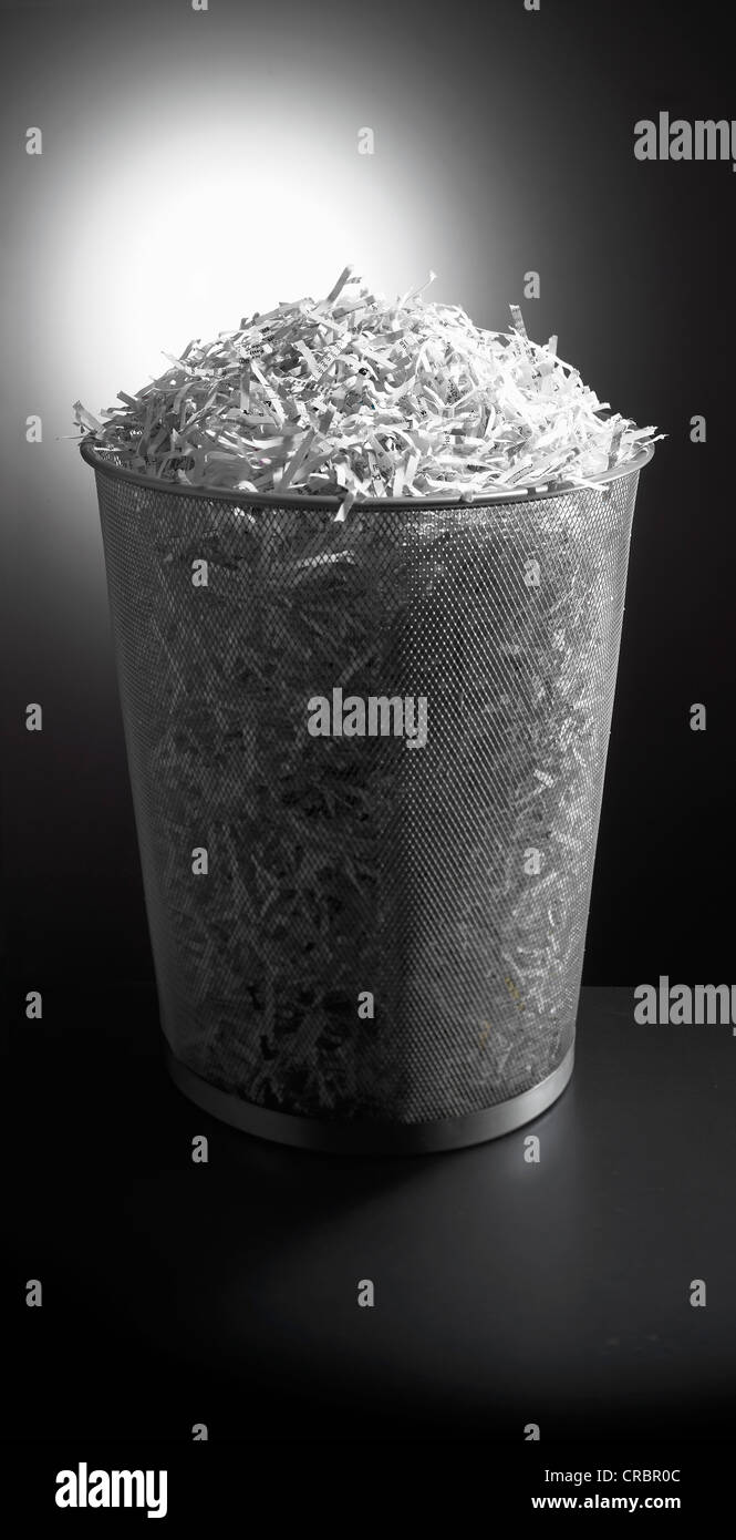 Trash can full of shredded paper - Stock Image
