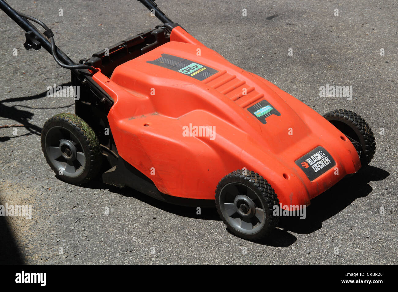 Orange rechargeable lawn mower - Stock Image