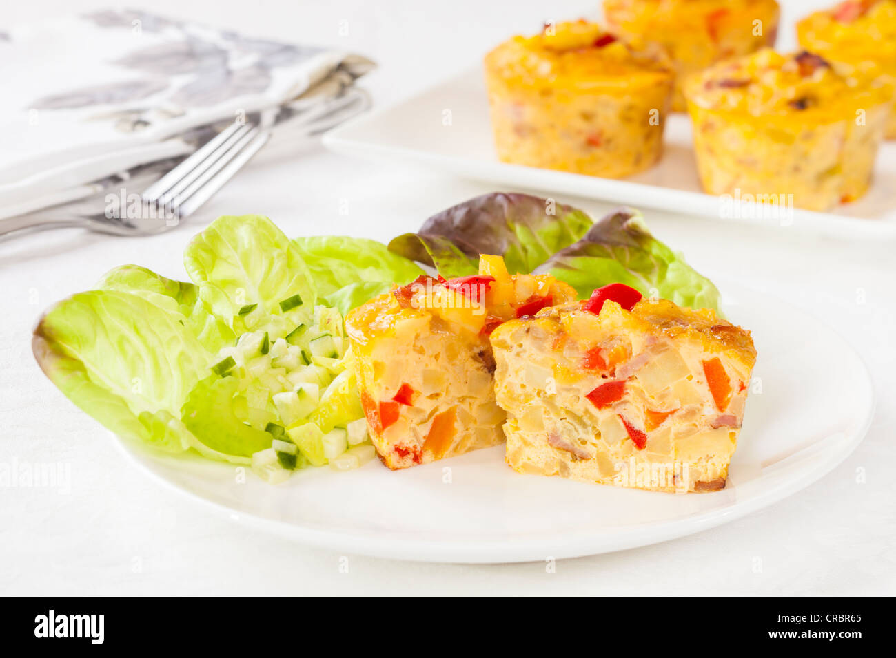Mini frittata on a plate with salad. - Stock Image