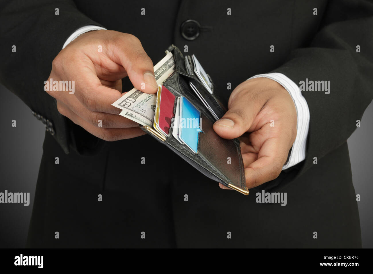 Businessman counting money in wallet - Stock Image