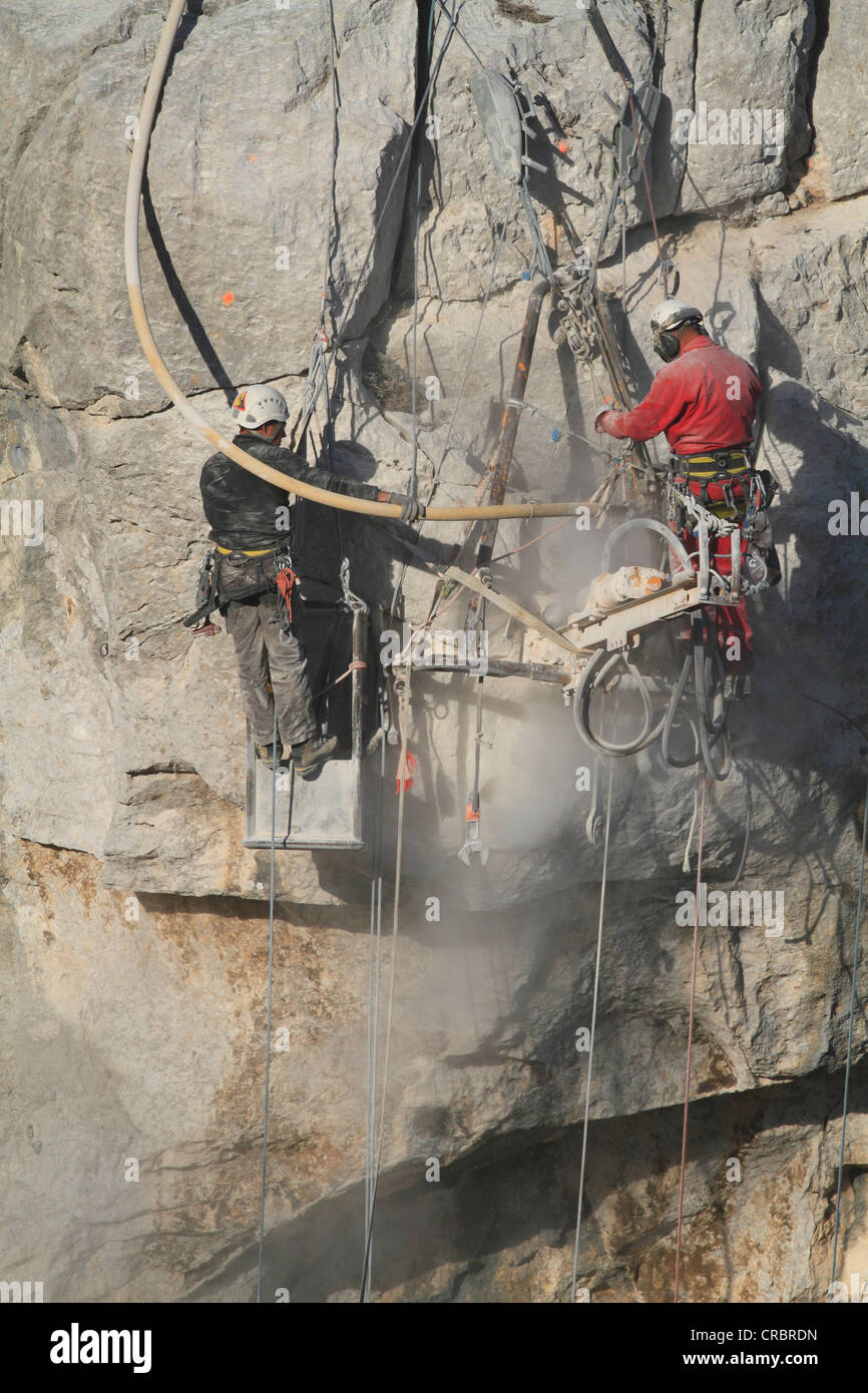 Workers safeguarding a cliff with jackhammers against landslides, loose rock is blasted off, La Turbie above Monaco, - Stock Image