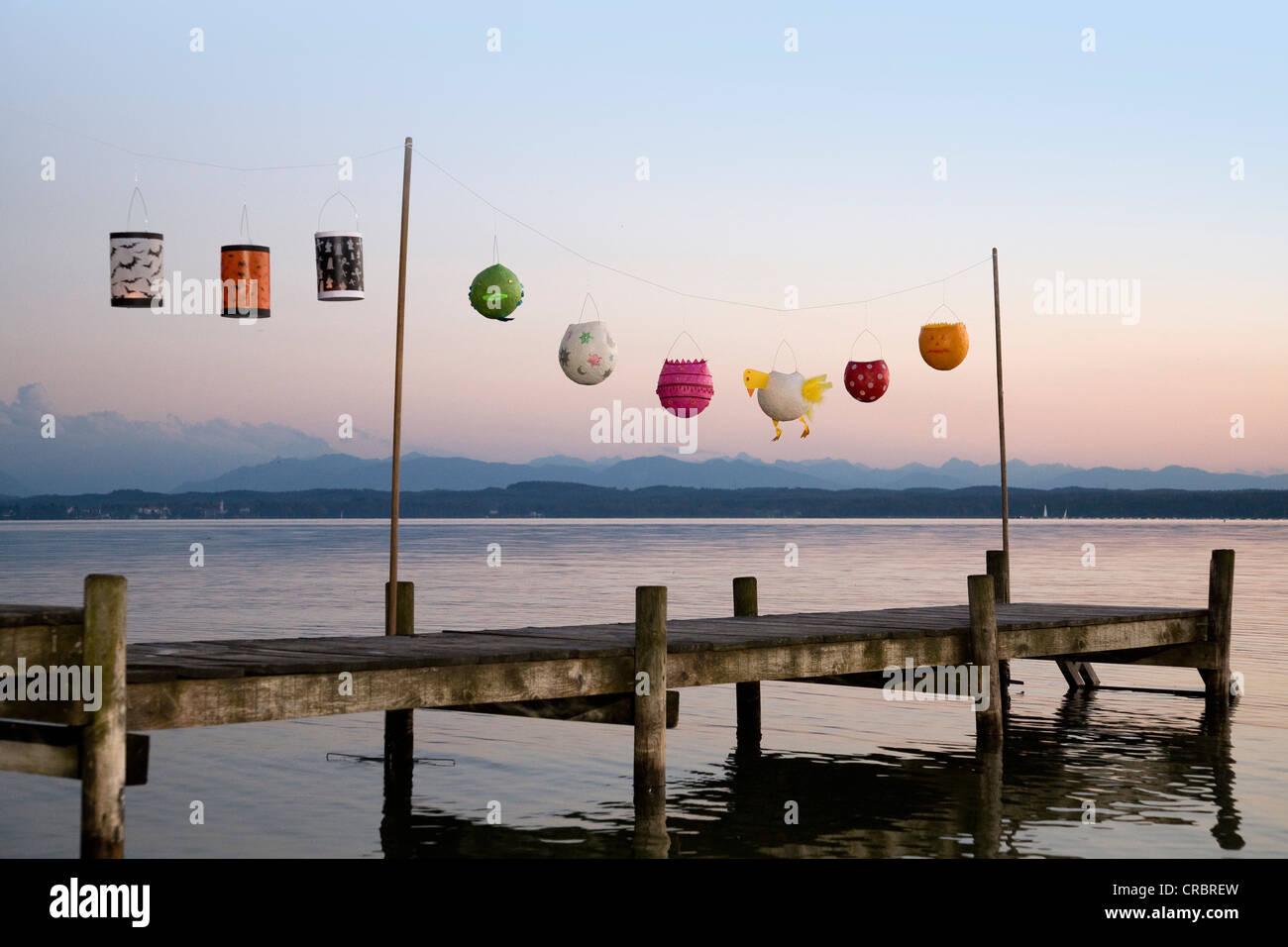 Paper lanterns strung up on wooden pier - Stock Image