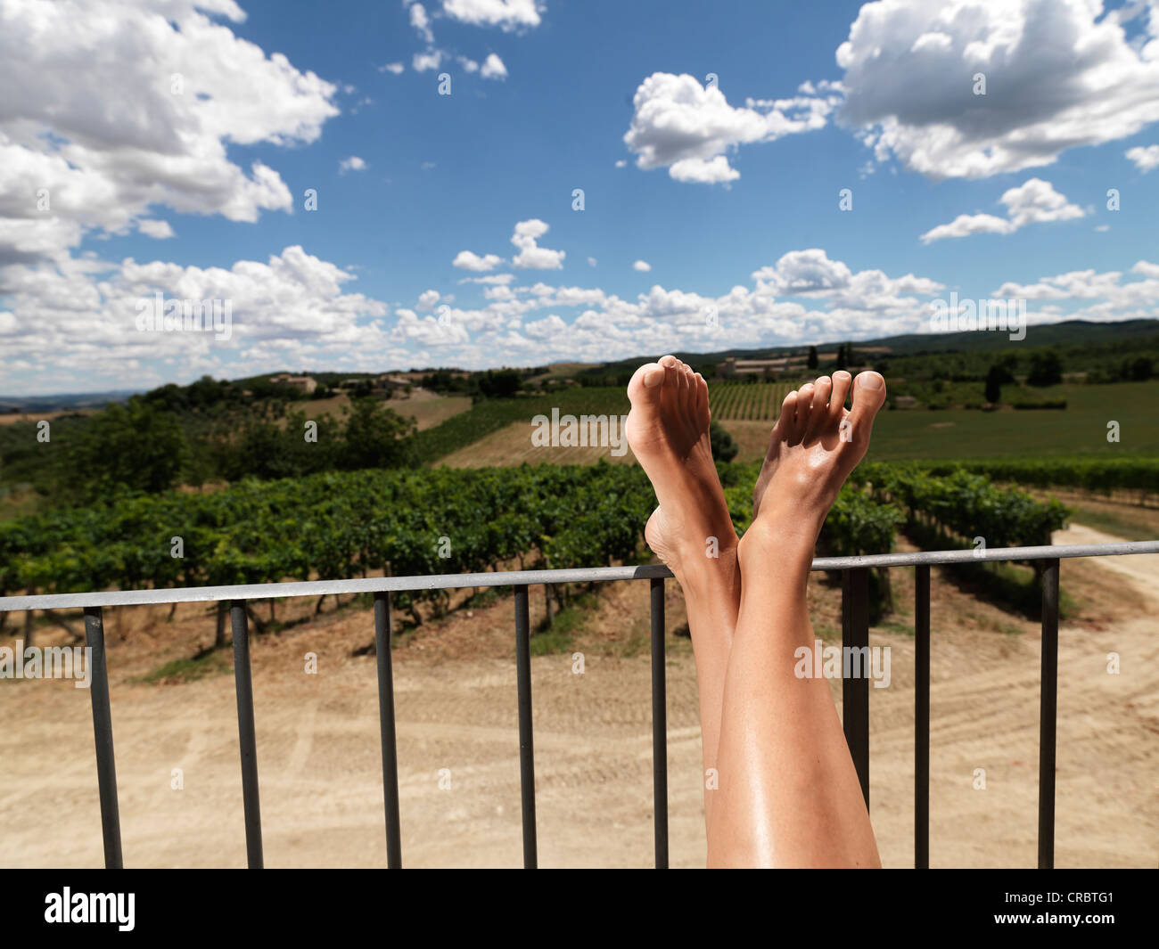Woman resting feet on railing outdoors - Stock Image