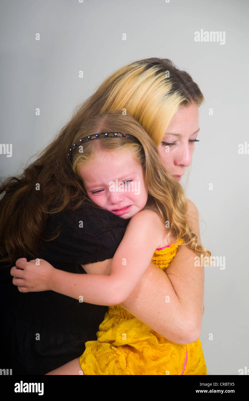 Mother comforting crying girl - Stock Image