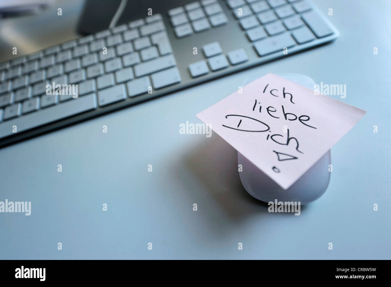 Sticky note with the words 'Ich liebe Dich', German for 'I love you', next to computer keyboard, - Stock Image