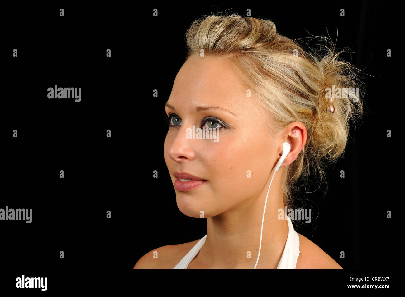 Young woman listening to music with an mp3-Player, earphones, headphones, Apple iPod, iPhone - Stock Image