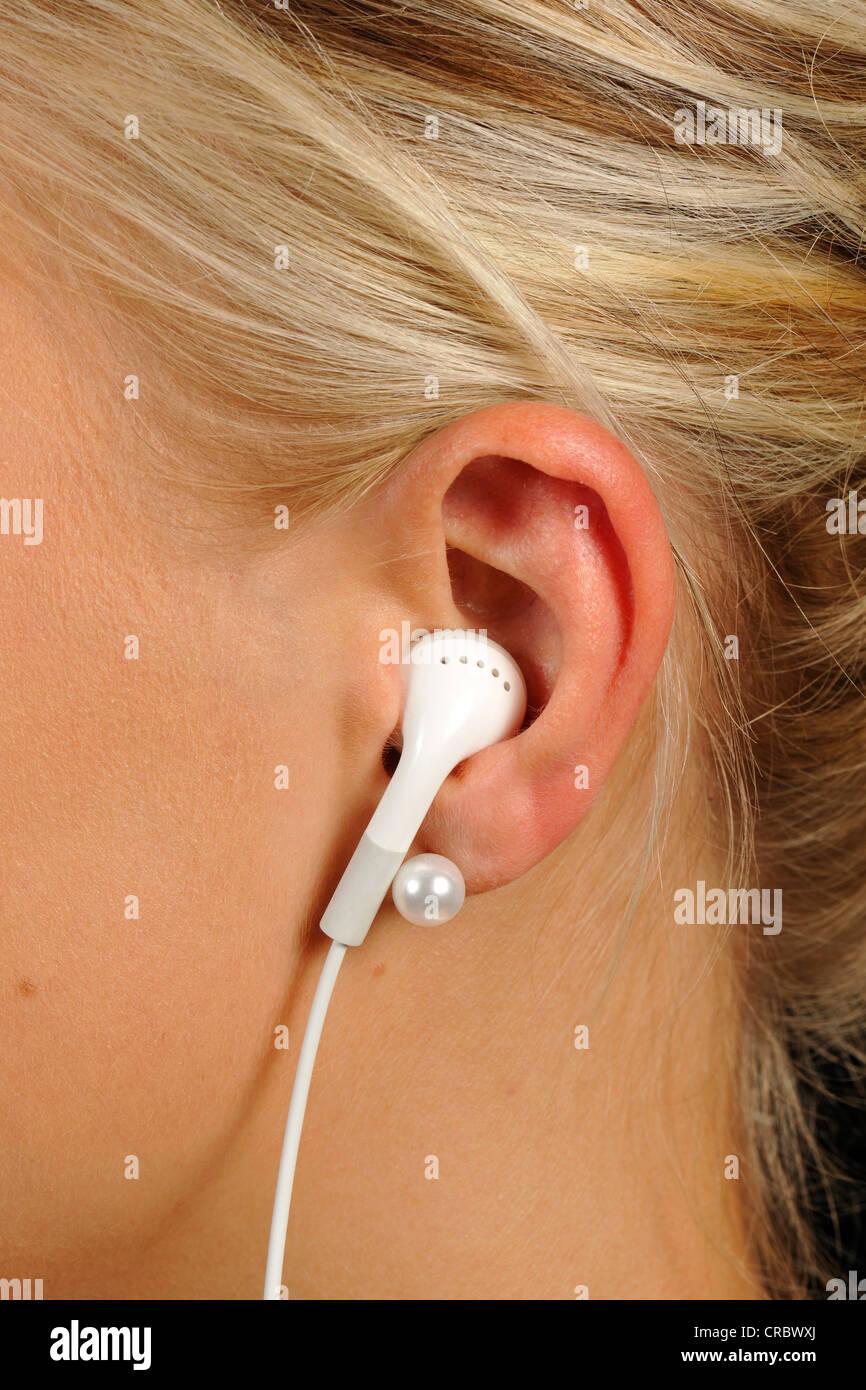 Young woman wearing earphones, headphones, Apple iPod, iPhone - Stock Image