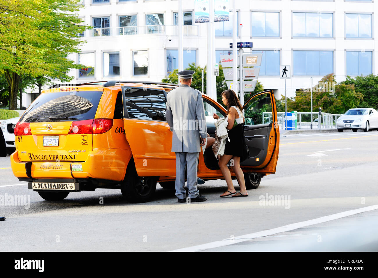 A woman getting into a taxi outside of an in Vancouver. - Stock Image