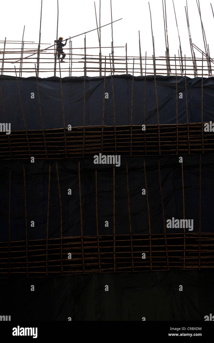 Worker constructing a bamboo scaffolding, Hong Kong, China, Asia - Stock Image