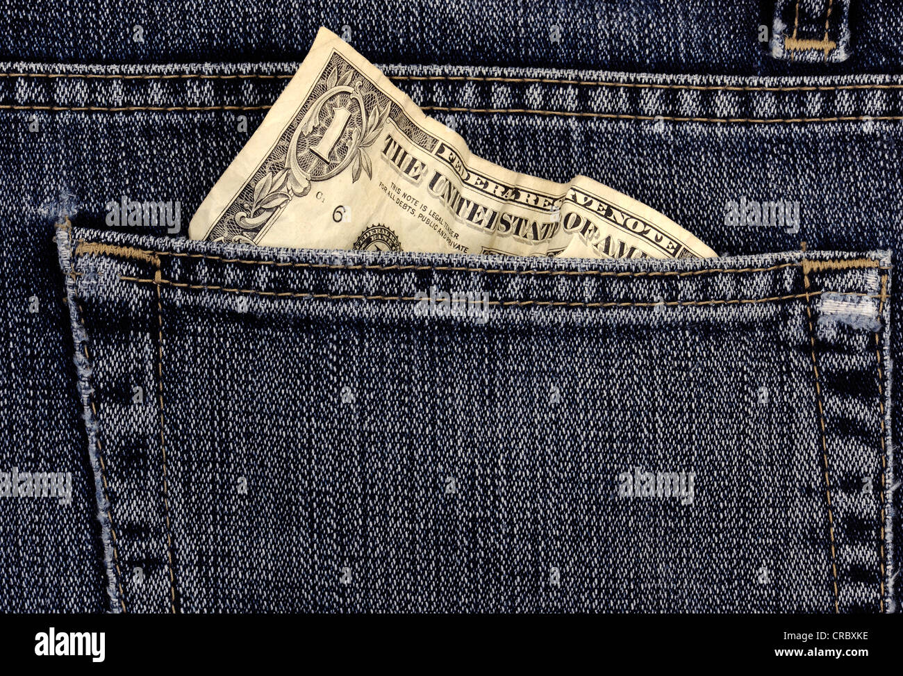 Crumpled 1 US dollar bill in a jeans pocket - Stock Image