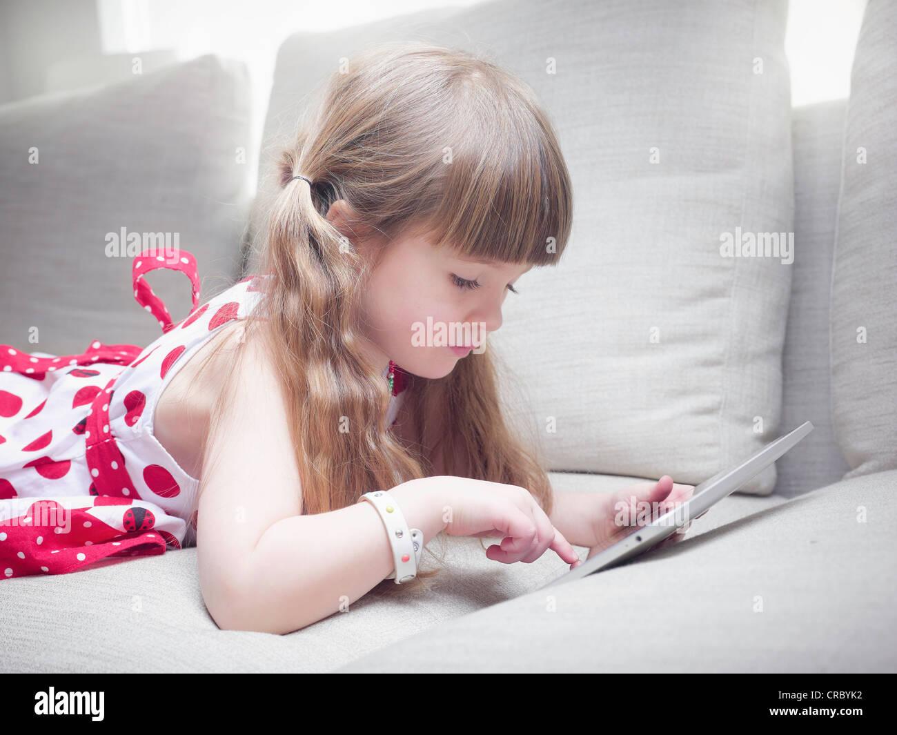 Girl using tablet computer on sofa - Stock Image