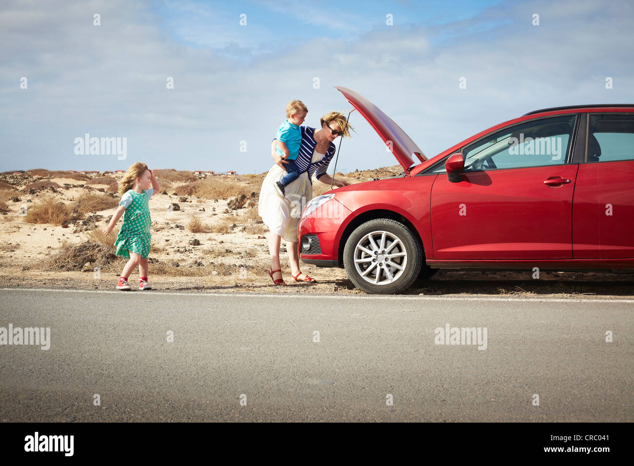 Mother examining broken down car - Stock Image