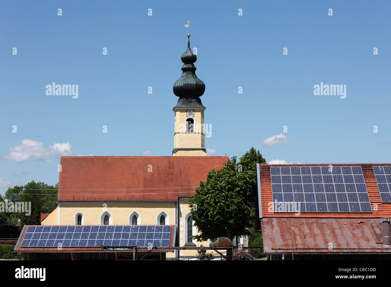 Church of the Nativity behind barnroofs with solar panels, Frauenried, Irschenberg district, Upper Bavaria, Bavaria - Stock Image