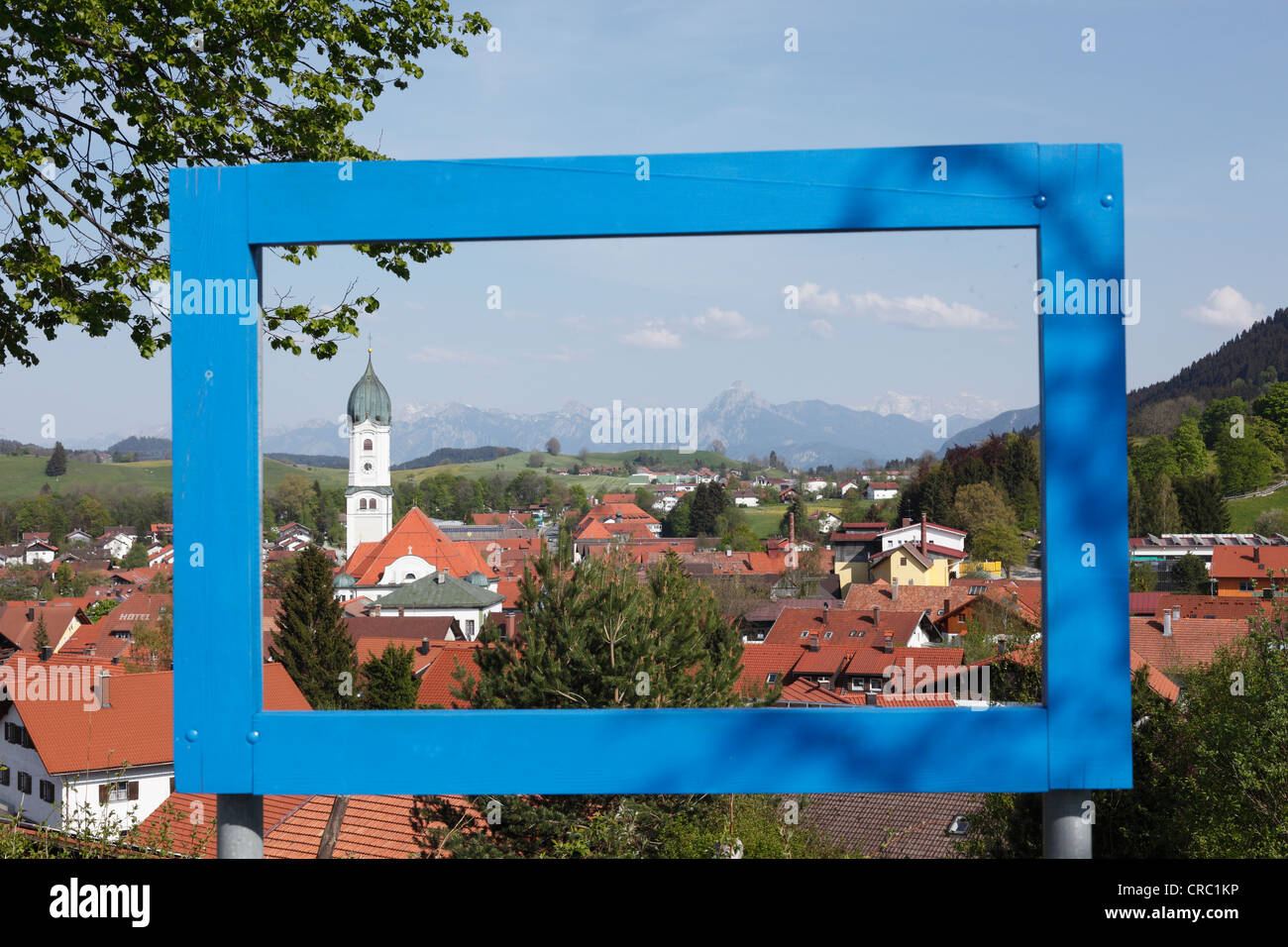 View on Nesselwang through a blue frame, Eastern Allgaeu, Allgaeu, Swabia, Bavaria, Germany, Europe, PublicGround - Stock Image