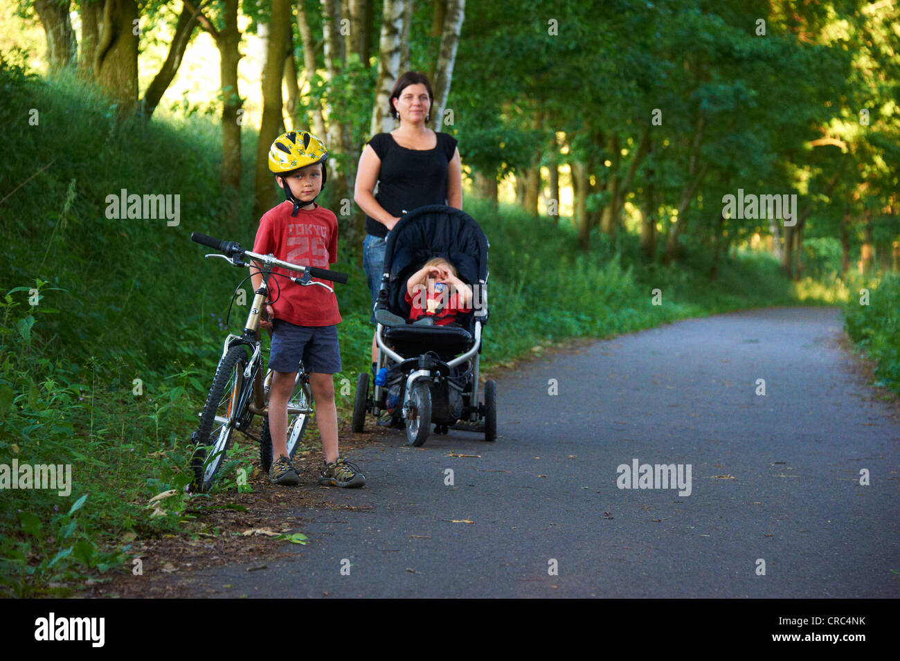 Child blond boy 6 - 7 years old riding bicycle with safety helmet in