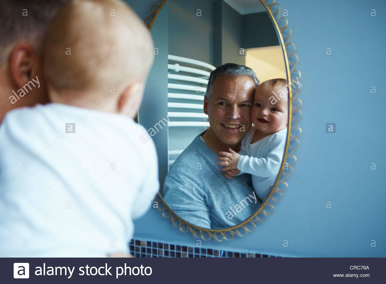 Father and baby admiring themselves - Stock Image