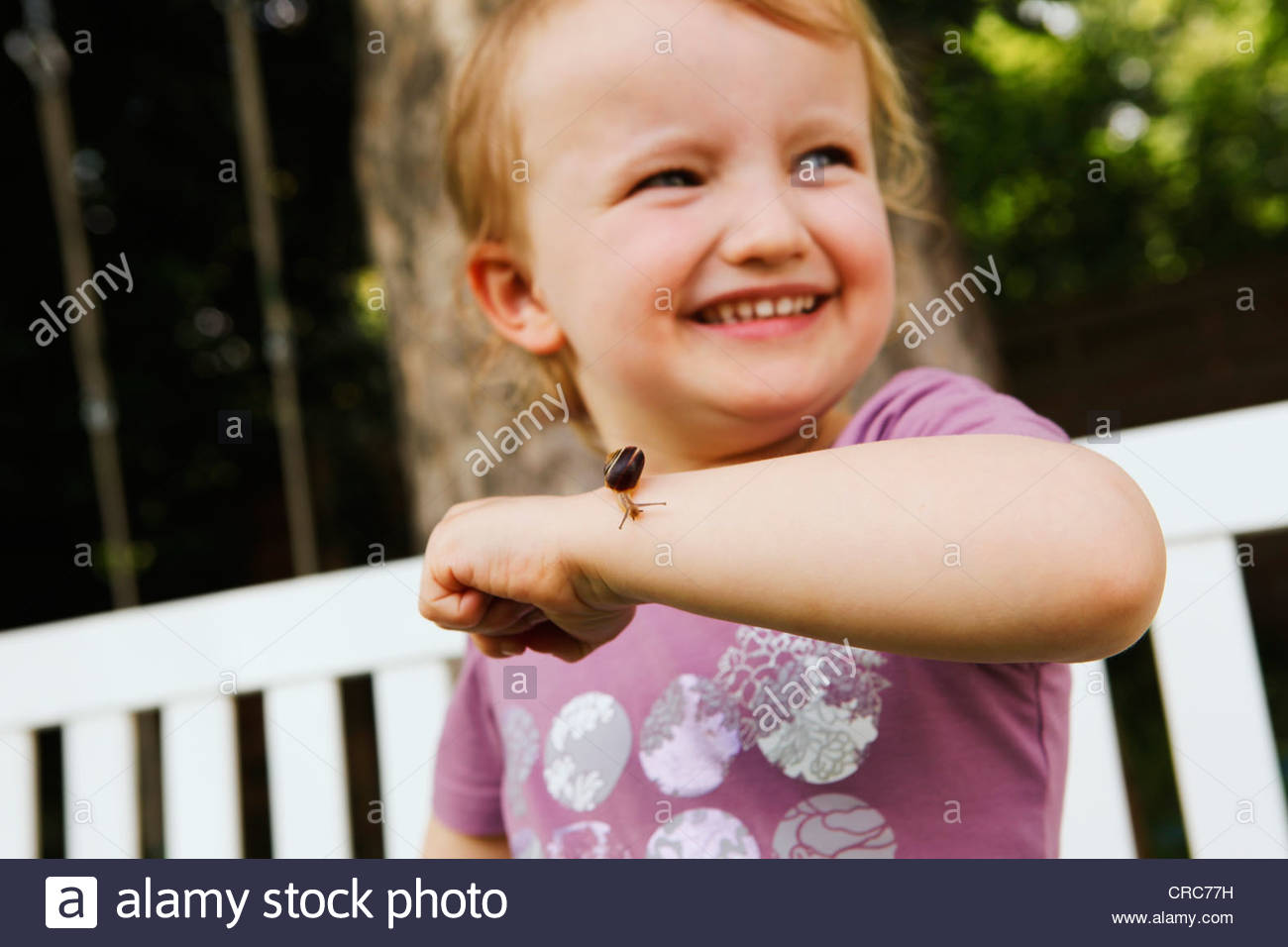 Girl holding snail on arm - Stock Image