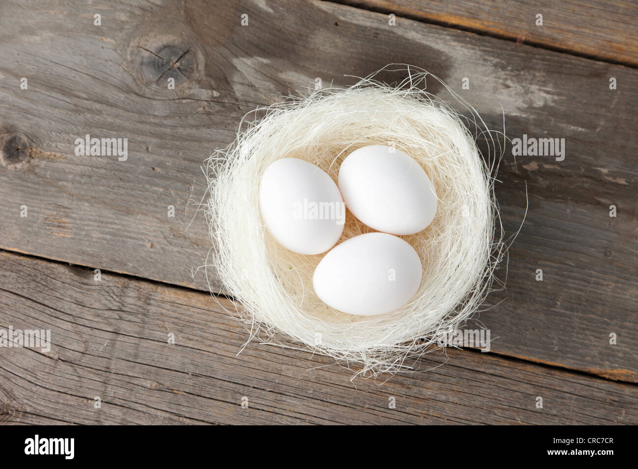 Eggs in nest on wooden counter - Stock Image