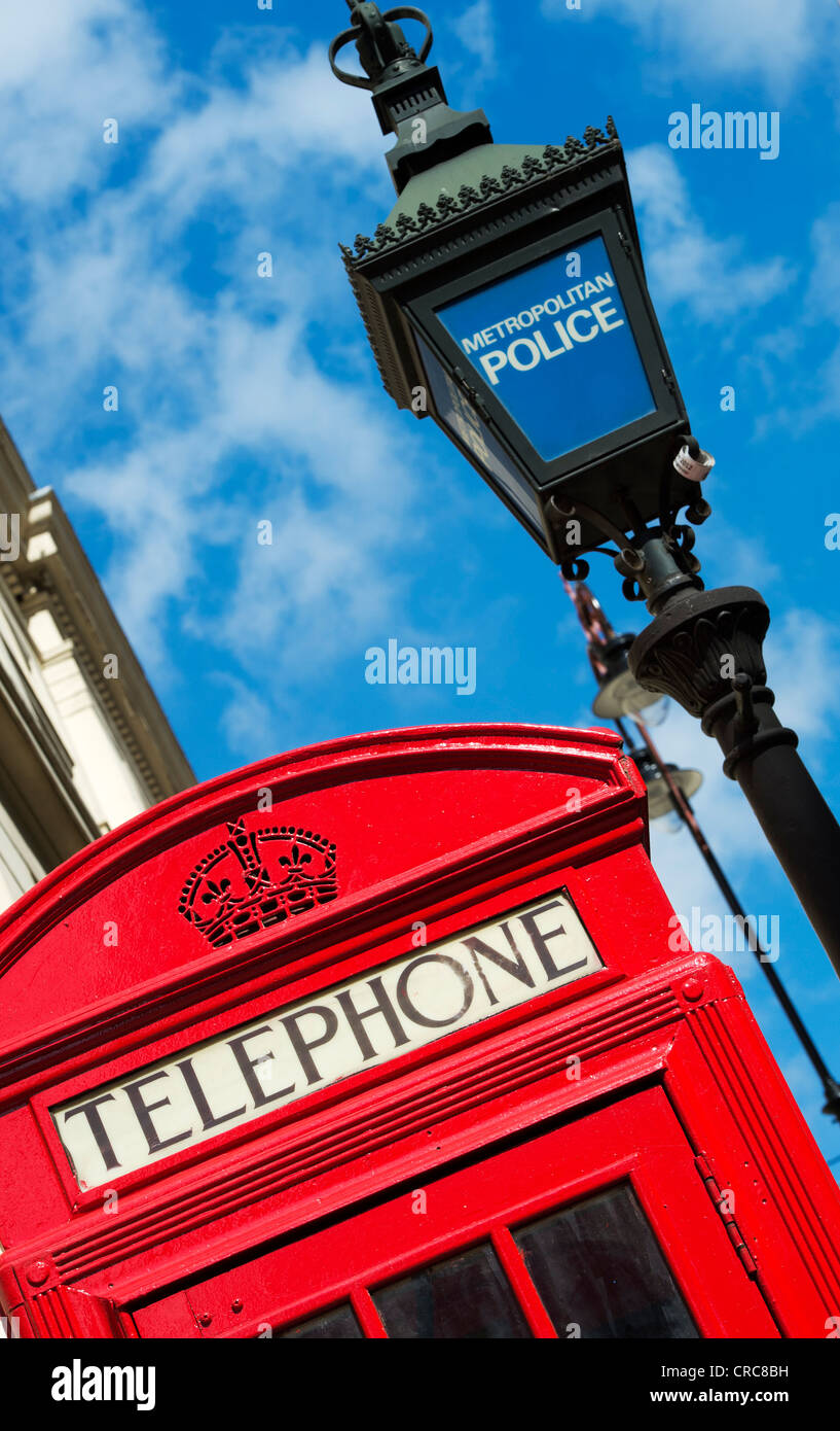 Metropolitan Police light and red telephone box against blue sky. London, England - Stock Image