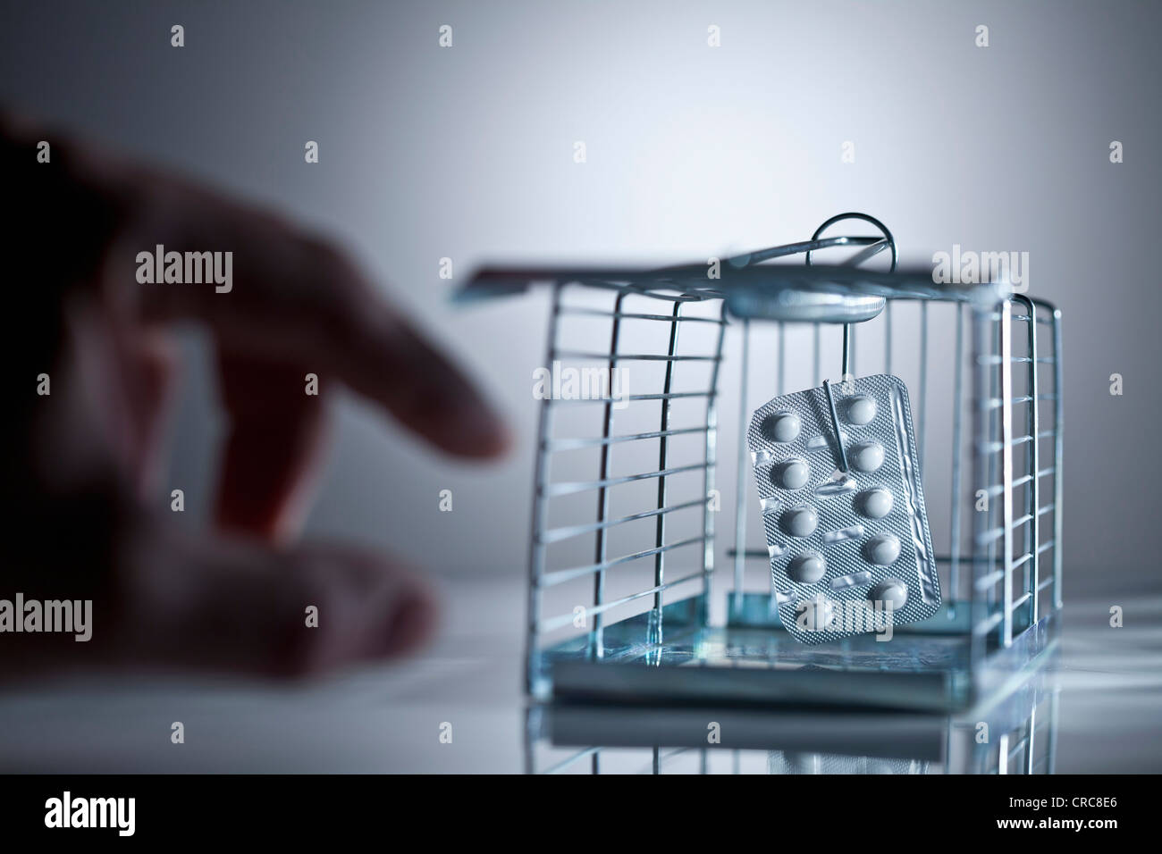 Blister pack of pills in cage trap - Stock Image