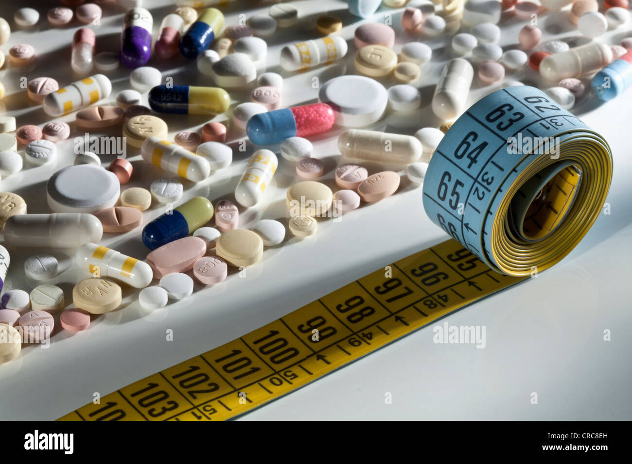 Scattered pills and measuring tape - Stock Image