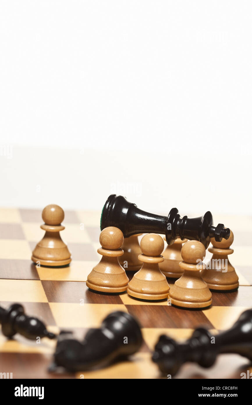 White pawns surrounding black chess king - Stock Image