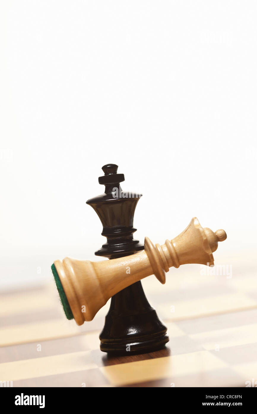 Black chess king holding white queen - Stock Image