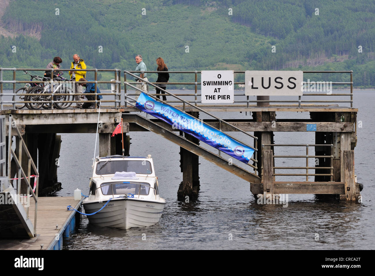 Visitors/tourists are attracted to beautiful Luss village and the pier,  Loch Lomond, Argyll, Scotland - Stock Image