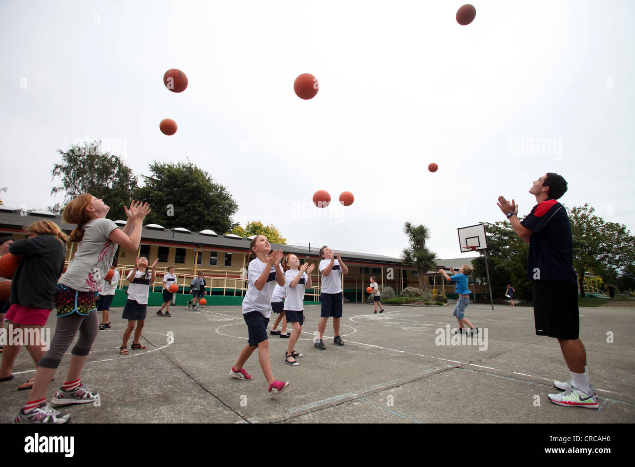 children having lessons in basketball by professional Ben Wright, a member of the Nelson Giants team, Richmond, - Stock Image
