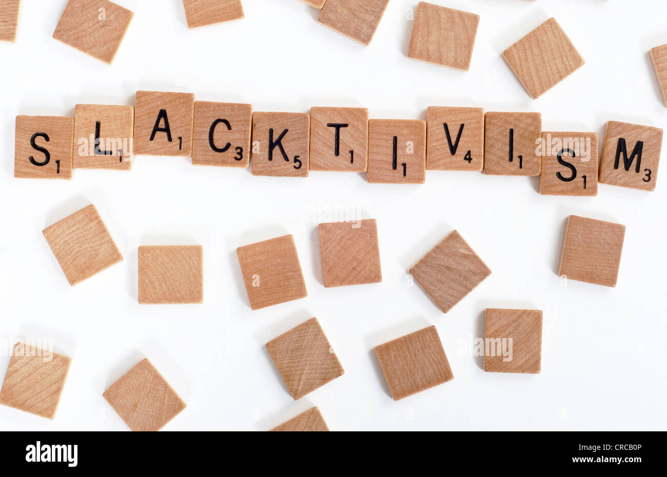 Wood Scrabble tiles spelling out the words 'Slacktivism'. On white - Stock Image