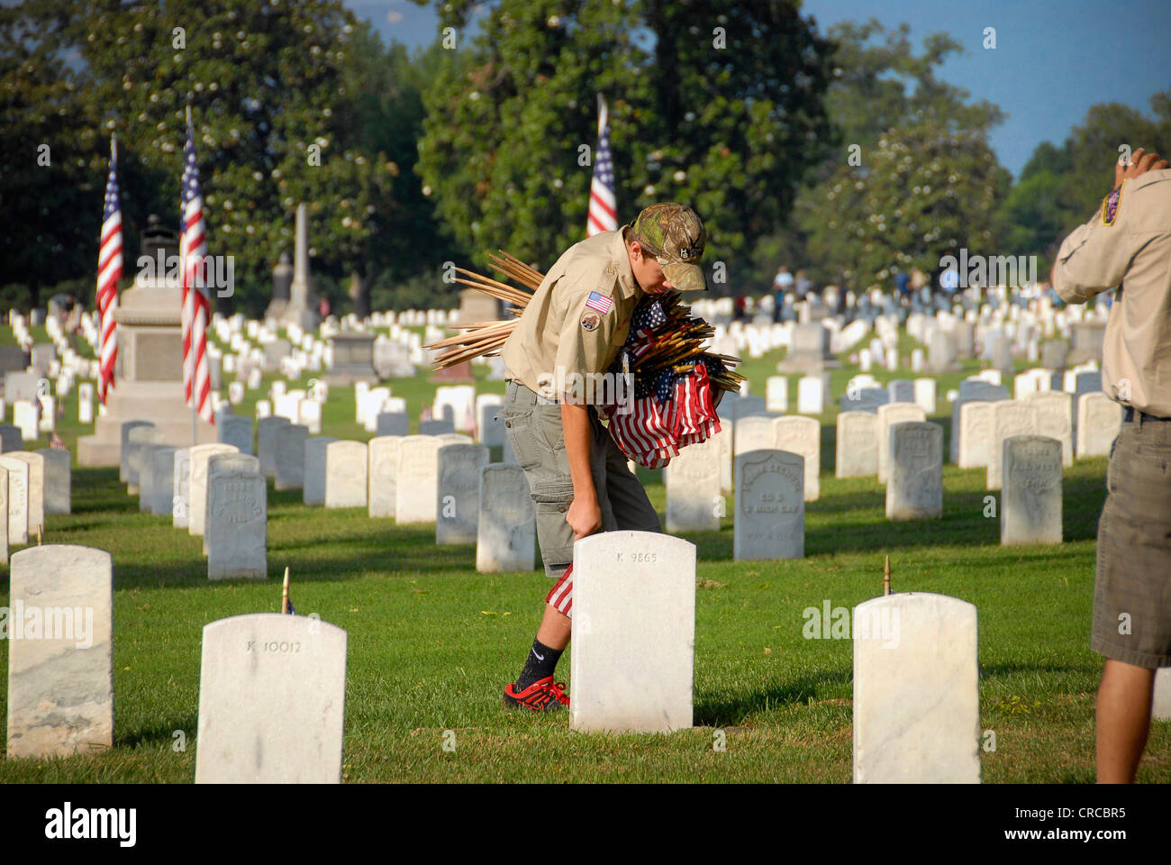 Boy Scout placing American flags at Chattanooga National Cemetery, Memorial Day 2012 - Stock Image